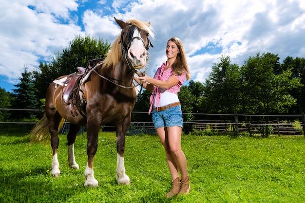 Young woman on the meadow with horse Premium Photo
