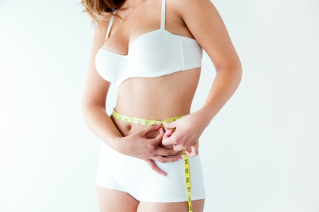 Young woman measuring her waist by measure tape. Free Photo