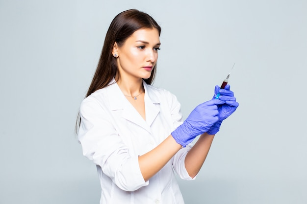 Young woman medic with a syringe in her hand on white wall. Free Photo