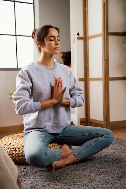 Giovane donna meditando a casa Foto Gratuite