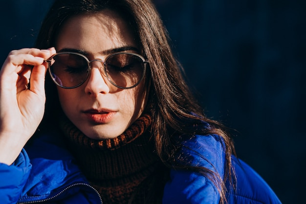 Young woman model in blue winter jacket on a blue background Free Photo