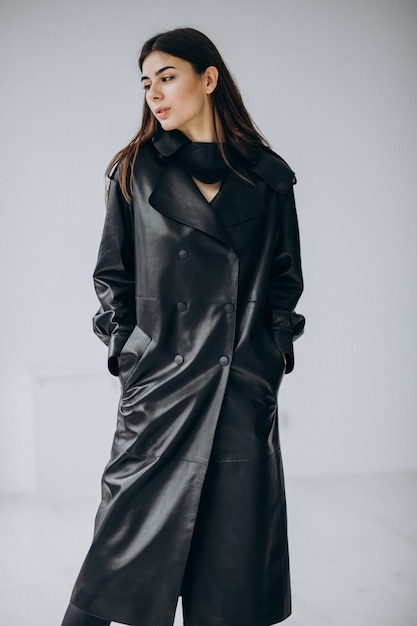 Young woman model wearing long black leather coat Free Photo