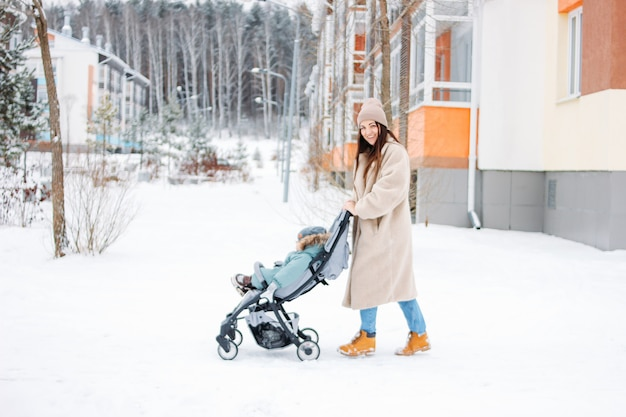 Young woman mother with child baby boy in stroller walking on winter street Premium Photo