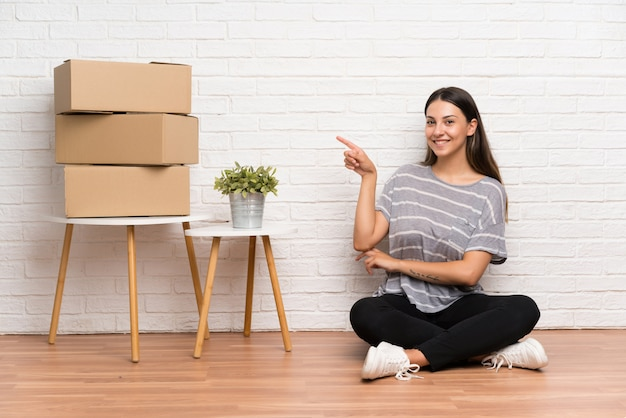 Young woman moving in new home among boxes pointing finger to the side Premium Photo