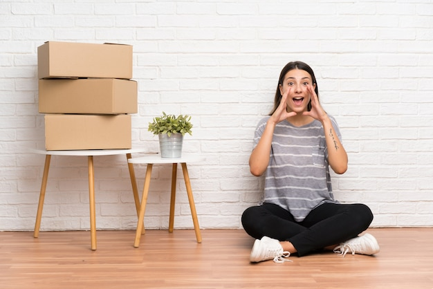 Young woman moving in new home among boxes shouting with mouth wide open Premium Photo