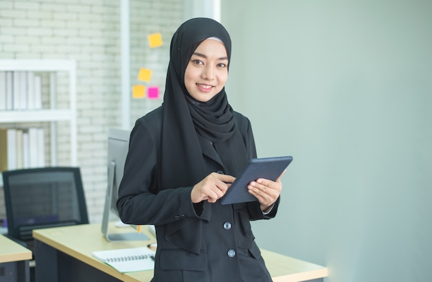 Young woman muslim work in office using phone Premium Photo