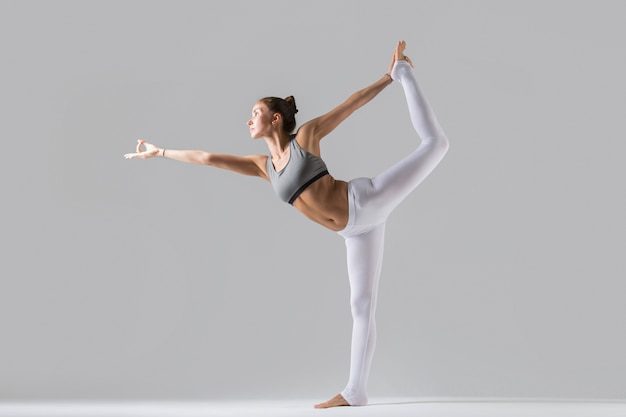 Young woman in natarajasana pose, grey studio background Free Photo