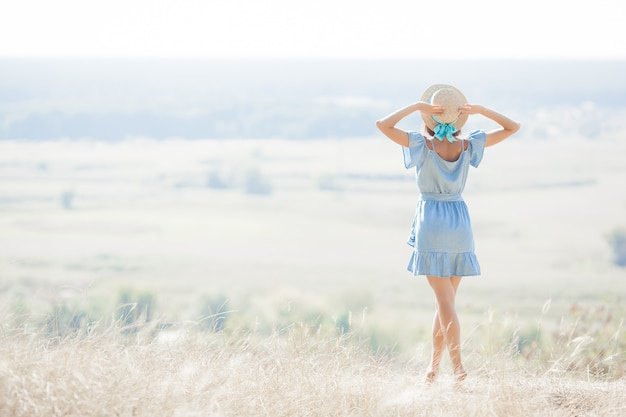 Young woman on nature  freedom. female free.  lady admires amazing natural view. woman admires a landscape. Premium Photo
