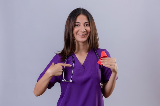 Infermiera della giovane donna che indossa l'uniforme e con lo stetoscopio che tiene il nastro rosso un simbolo della lotta contro l'aids che punta ad esso con il dito indice sorridente amichevole Foto Gratuite