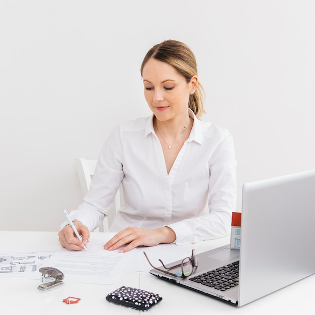Young woman in office doing paperwork in front of laptop Free Photo