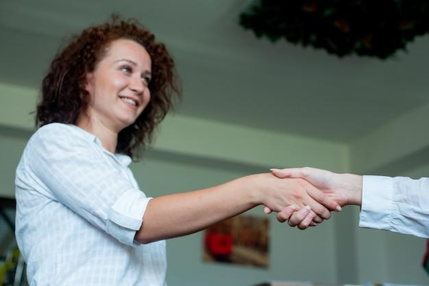 同僚がオフィスに立っているとフレンドリーな握手を笑顔若い女性会社員 無料写真