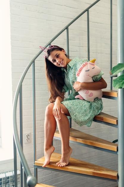 モダンな家の木製の階段の若い女性。 無料写真