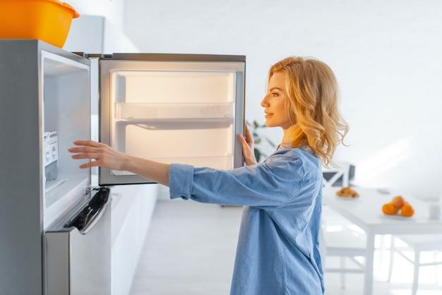 Молодая женщина открыла холодильник на кухне. Premium Фотографии