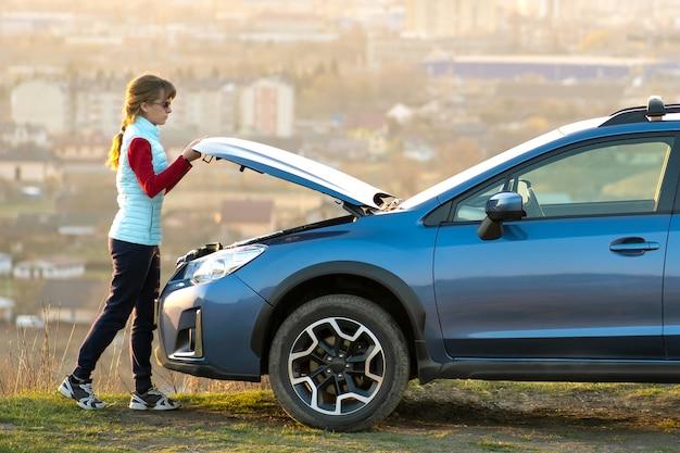 Молодая женщина, открыв капот сломавшегося автомобиля, возникли проблемы с ее транспортным средством Premium Фотографии