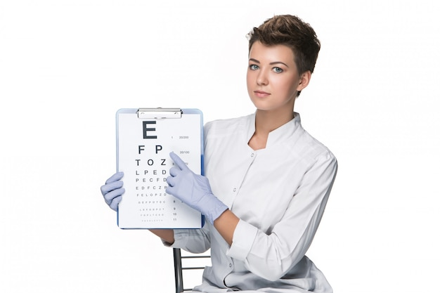 Young woman ophthalmologist with eye chart Free Photo