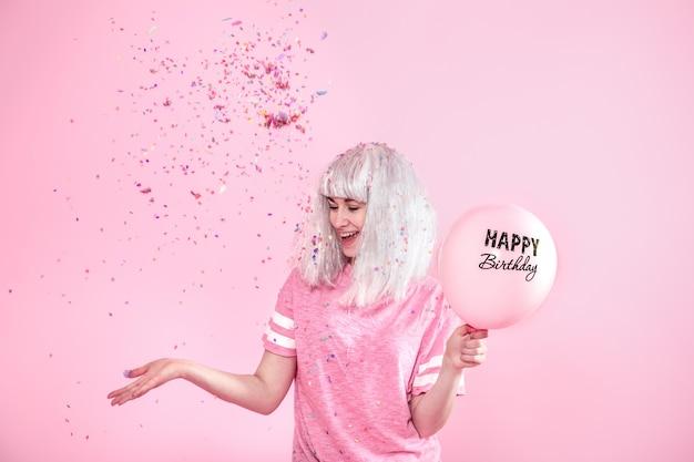 젊은 여자 또는 소녀 풍선 생일 축하합니다. 위에서 색종이를 던집니다. 휴일 및 파티 개념. 프리미엄 사진