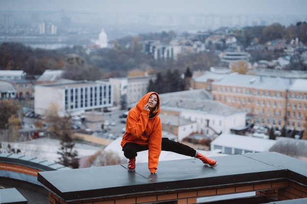 Young woman in an orange sweatshirt poses on the roof of a building in the city center Free Photo