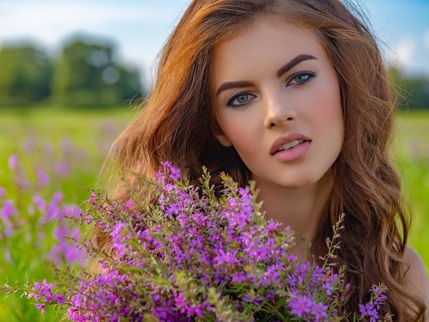 花束を持つ屋外の若い女性。彼女の手にラベンダーの花を持つフィールドの女の子。自然の白人女性のクローズアップの肖像画。 無料写真