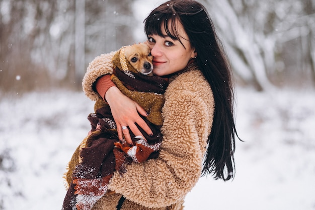 Young woman outside the park with her little dog at winter Free Photo