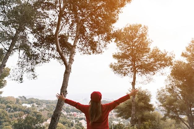Молодая женщина, протягивая руки, глядя на пейзаж Бесплатные Фотографии