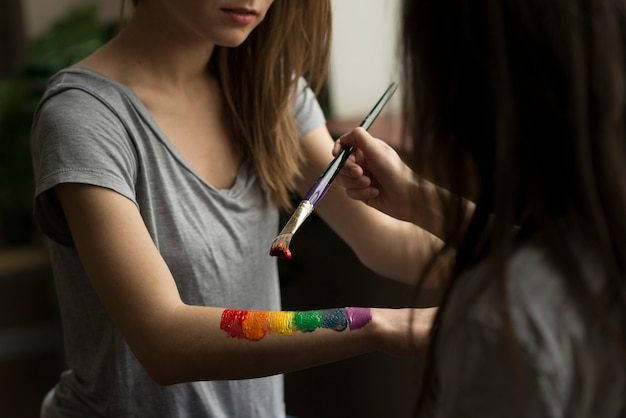Young woman painting the rainbow flag over her girlfriend's hand with paintbrush Free Photo