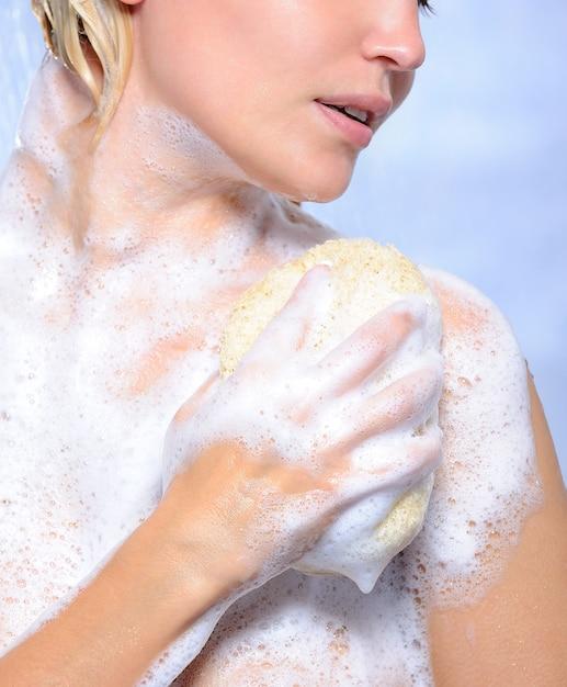 Молодая женщина балует свое тело губкой и мыльной пеной Бесплатные Фотографии