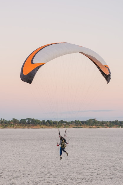 Young woman parachuting down to the ground riverside Premium Photo