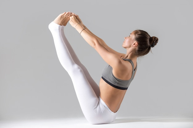 Young woman in paripurna navasana pose, grey studio background Free Photo