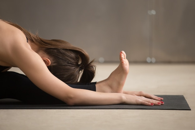 Young woman in paschimottanasana pose, grey studio background, c Free Photo