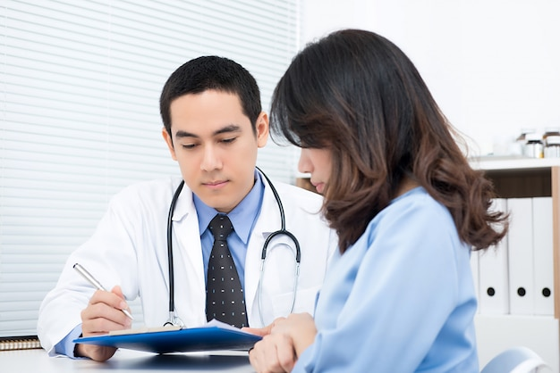 Young woman patient consulting with asian male doctor Premium Photo