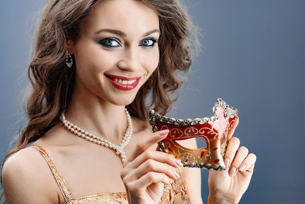 Young woman in a pearl necklace smiles holds a carnival mask in her hand close-up Premium Photo