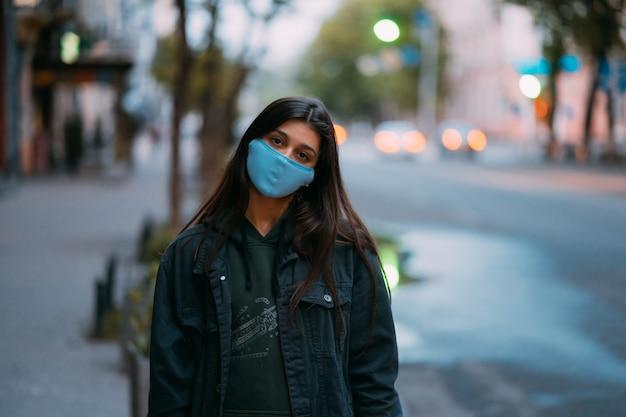 Giovane donna, persona in maschera protettiva sterile medica in piedi in strada vuota, guardando la fotocamera. Foto Gratuite