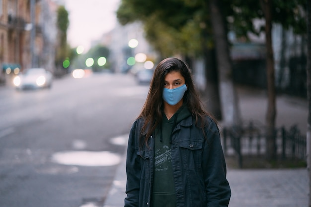 Young woman, person in protective medical sterile mask standing at empty street, Free Photo