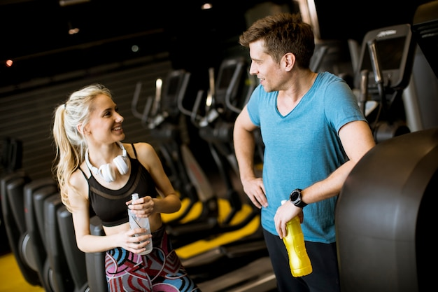 Young woman and personal trainer rest in the gym after workout Premium Photo
