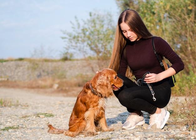 Young woman petting a cocker spaniel Free Photo