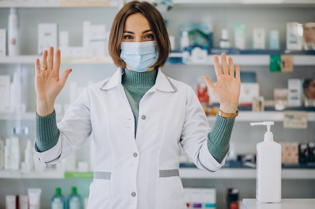 Farmacista della giovane donna che disinfetta le mani con disinfettante Foto Gratuite