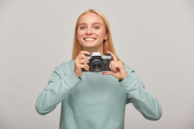 Молодая женщина-фотограф выглядит счастливо улыбается, держа в руках ретро-фотоаппарат Бесплатные Фотографии