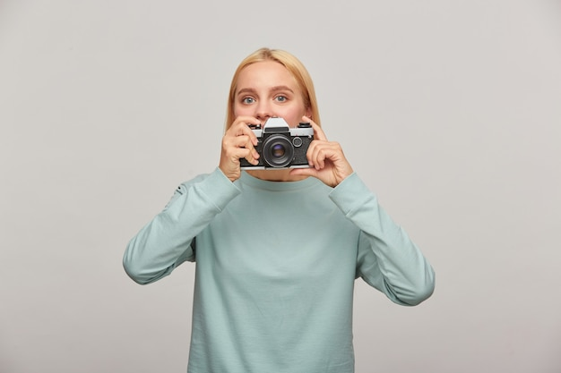 Young woman photographer looks out from behind the lens, holding a retro vintage photo camera Free Photo