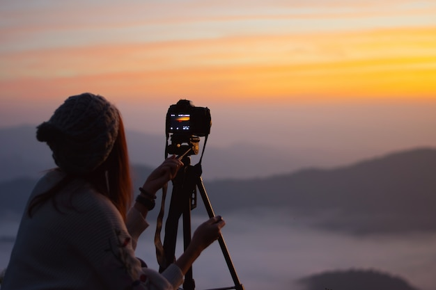 Young woman photographer taking picture of landscape when sunrise  at mountain peak. Premium Photo