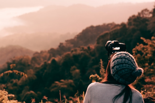 Young woman photographer taking picture of landscape when sunrise  at mountain peak Premium Photo