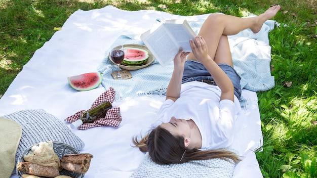 Una giovane donna a un picnic leggendo un libro Foto Gratuite