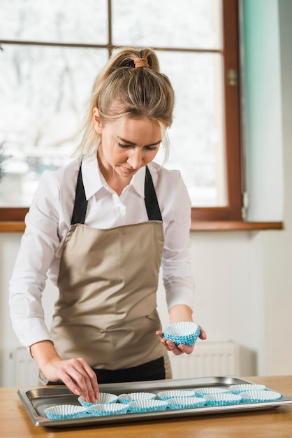 Young woman placing an empty baking cups in the tray on wooden table Free Photo
