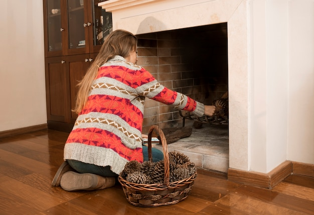 Young woman placing pinecone in the fireplace Free Photo