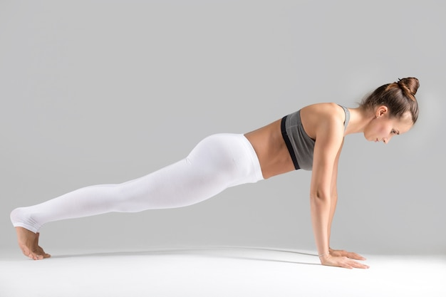 Young woman in plank pose, grey studio background Free Photo