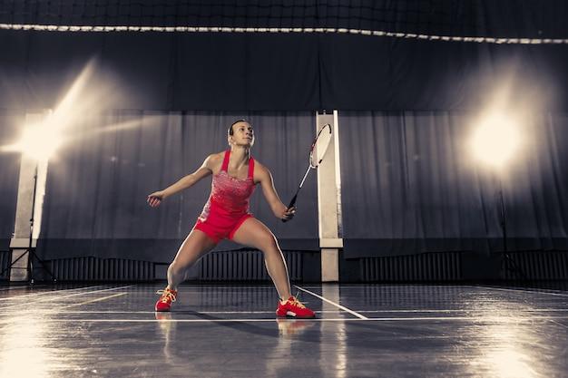 Молодая женщина играет в бадминтон в тренажерном зале Бесплатные Фотографии