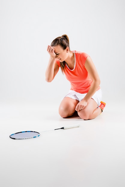 Молодая женщина играет в бадминтон на белой стене Бесплатные Фотографии