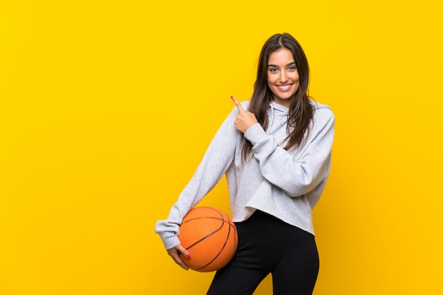 Young woman playing basketball over isolated yellow wall pointing to the side to present a product Premium Photo