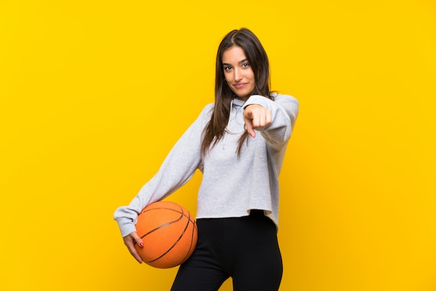 Young woman playing basketball over isolated yellow wall points finger at you with a confident expression Premium Photo