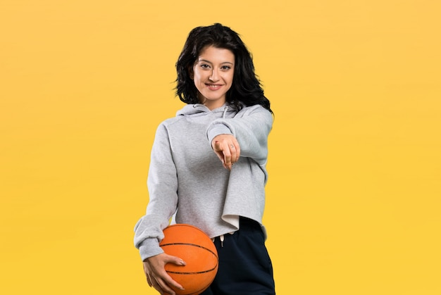 Young woman playing basketball points finger at you with a confident expression Premium Photo