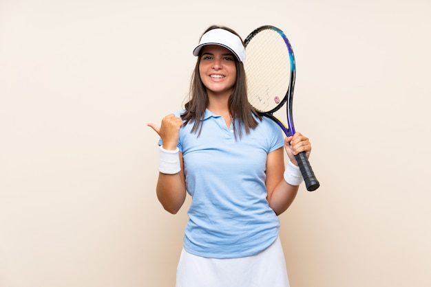 Young woman playing tennis over isolated wall pointing to the side to present a product Premium Photo
